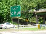 An image of Exit 2B and a curves ahead sign on the other road