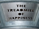 "Photo of an engraved ""the treadmill of happiness"" sign"